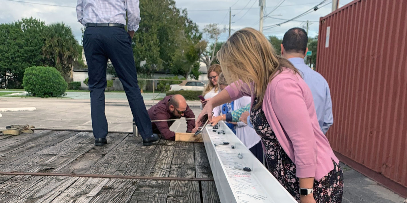 teammates signing final beam to used in construction
